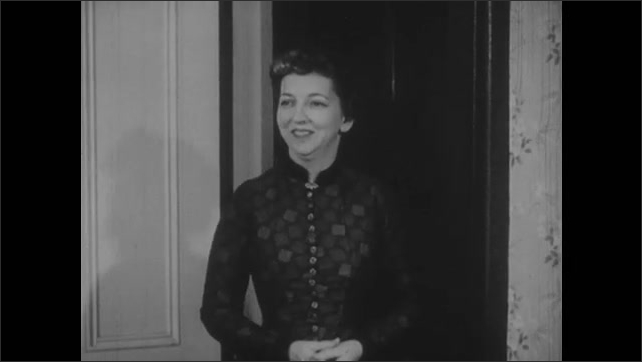 1950s: Woman gets up from chair, walks away from young girl at table. Woman walks into room, smiles. Young woman plays piano, young man stands beside her.