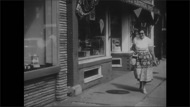 1950s: Large building. People walk down city sidewalk. Woman walks out of building, stops and looks in book store window. Display of feminist books.
