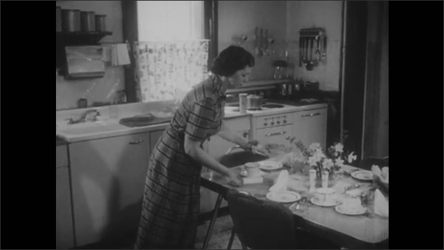 1950s: Farmer drives tractor across field. Farmhouse. Woman sets table, walks into living room. Woman sits in chair, reads book, woman sits in chair across from her, women talk.