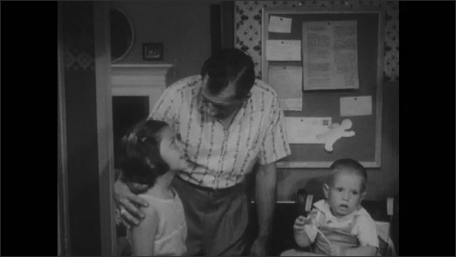1950s: Woman fills pot with water, sets pot on stove. Toddler sits in high chair, girl sits by stove. Man walks in, greets woman. Man talks to girl and woman. Man lifts toddler from seat.