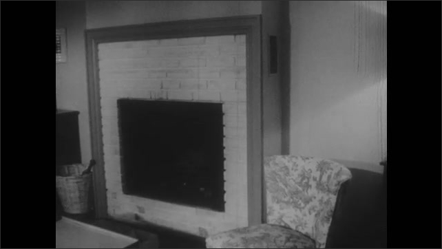 1950s: Man sits alone on couch, looks around room.