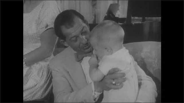 1950s: Man sits on couch, holds toddler. Woman and young girl stand nearby. Man talks to baby, woman talks to girl. People exit church, married couple walks down stairs enters car.