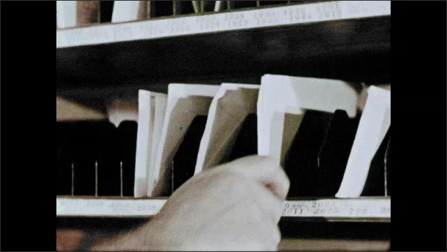 1950s: Man inspects gauges and writes on clipboard. Postal worker sorts letters into slots. Hand places letter in slot. Postal workers sort letters. Men and women work at desks in office.
