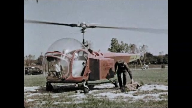 1950s: Man unlocks box on side of helicopter and places bag inside. Man locks box and carries bag away from helicopter. Helicopter lifts off ground. Passenger plane lands at airport.