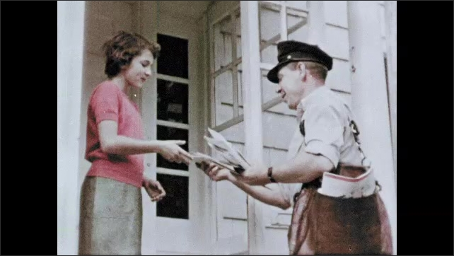 1950s: Text on second floor office window. Policeman walks past store. Man holds door for woman and children. Mailman delivers letter and talks to girl. Flag waves above government building.
