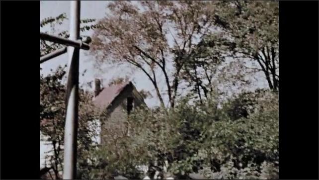 1950s: Boy kicks football. Children climb on jungle gym. Children and women in playground. Man plays tennis.