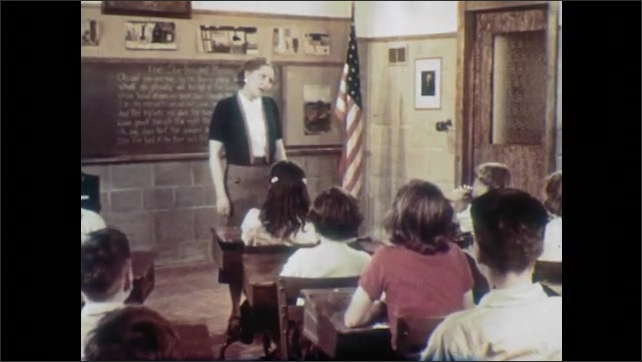 1950s: Students sit, smile and clap.  Teacher speaks to class.  Students raise hands.  Teacher calls on boy.