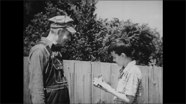 1950s: Men and boy stare at stone axe blade. Boy looks at artifact. Hand holds stone axe blade. Man talks to boy and shows him modern axe. Hands hold modern axe and stone axe blade.