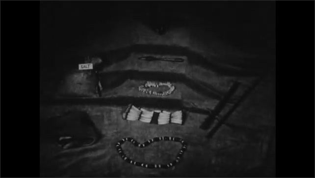 1950s: Man talks to boys outside of barn. Hand holds a number of coins. Native American beads and necklaces in museum display. Hand closes around coins.