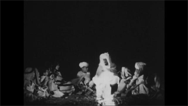 1950s: Bedouin man talks t children around campfire. Children smile and listen to man.