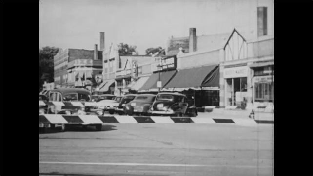 1950s: Cranes lift cargo onto ships at dock. Cars sit on road at trolley crossing in city. Trolley crosses road in city.
