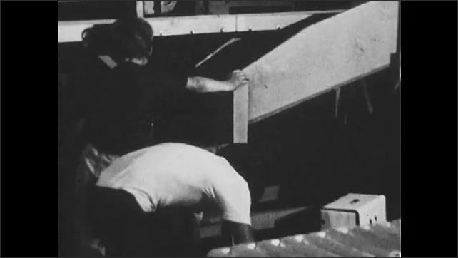 1970s: People push pallet of boxes towards truck. Boy moves crate of apples. Women sort fruit on conveyor belt.
