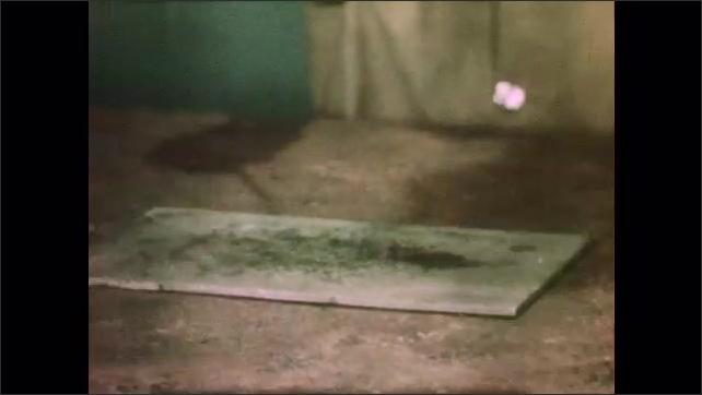 1940s: Man waves lit match over plate, flame flares up. Man takes lid of cylinder, lights match, lights candle inside cylinder, places lid on cylinder.