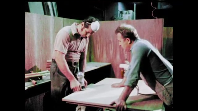1970s: Machine parts moving, zoom out to man at machine. Man sanding board. Man painting wood. Men cutting board. Man looking through pipe, zoom out to end of pipe. Man smoothing column.