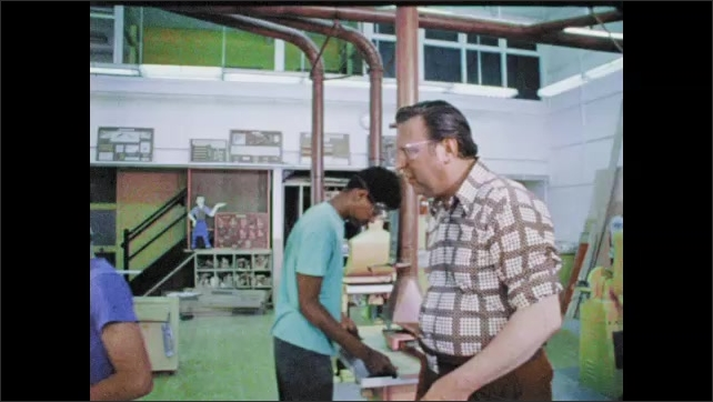 1970s: Man walks by girl working with drill. Close up of drill on wood. Hands mark wood with ruler. Man walks through workshop, talks to boys. Hands pushing wood through saw.