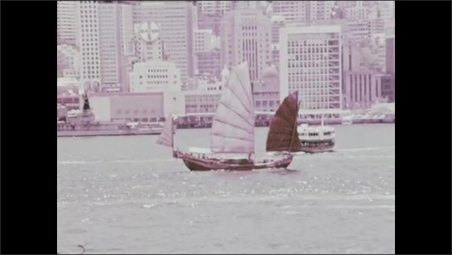 1970s: Boats sail on bay with city in background.