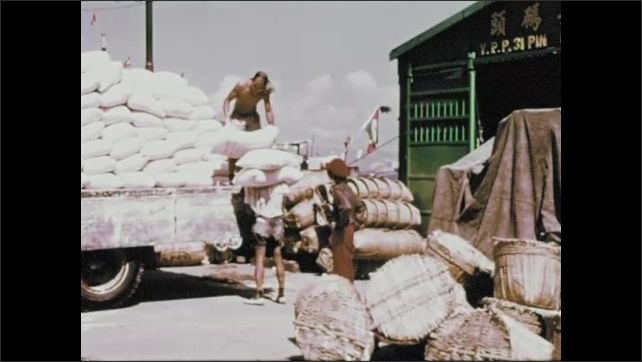 1970s: Workers transfer bags of goods to truck. Boy in hat watches workers on docks.