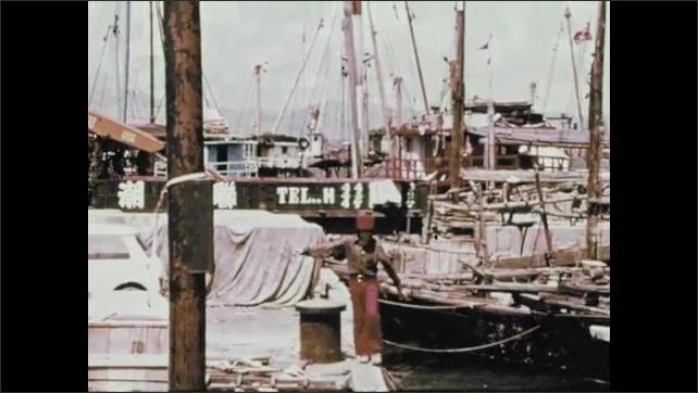1970s: Dockworkers at work. Boy walks along railing at dock. Fishing boats in bay near village.