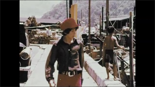 1970s: Fishing boats on bay. Boy walks along dock. Boy talks and points. Boy bows and hands money to woman.