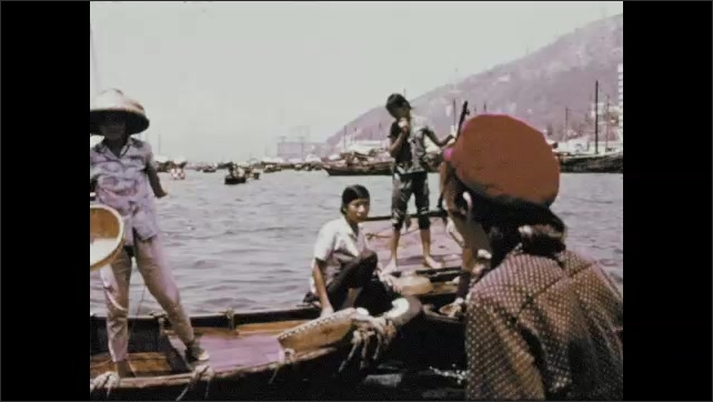 1970s: People on fishing boats. Children on boats hold straw baskets. Child jumps into water.