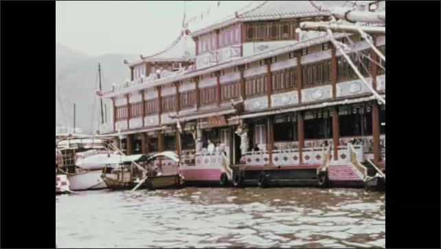 1970s: Girl holds umbrella and speaks. People on fishing boat. Boat passes by floating restaurant.
