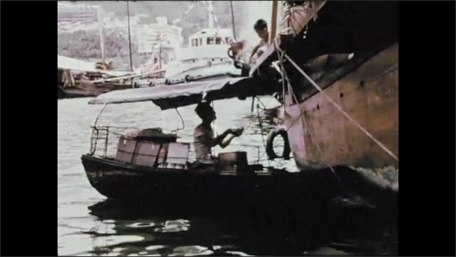 1970s: Worker steers fishing boat. Person on fishing boat hands food to person on larger boat.