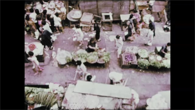 1970s: Boy walks through market. Boy stops and picks up fish in market. People at market.