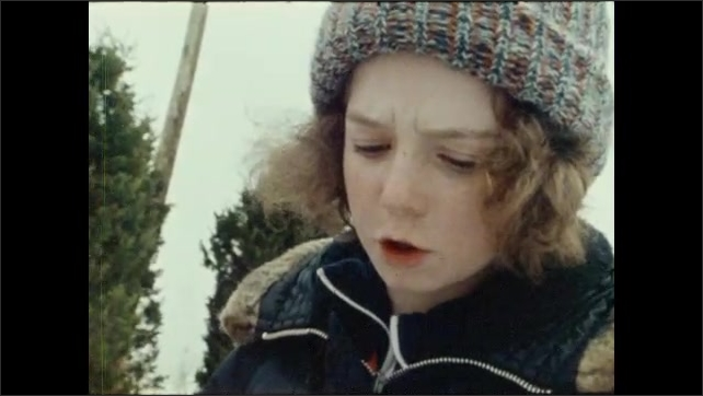 1970s: Children stand outside, talk to each other, Children pick up sleds, walk up hill.