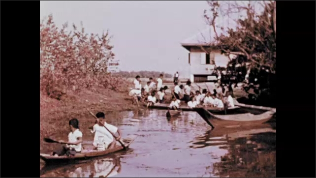 1970s: Woman stands in the middle of a circle of children, waves her arms. Children dance around woman. Children clap and sing. Children climb into canoes, paddle down river.