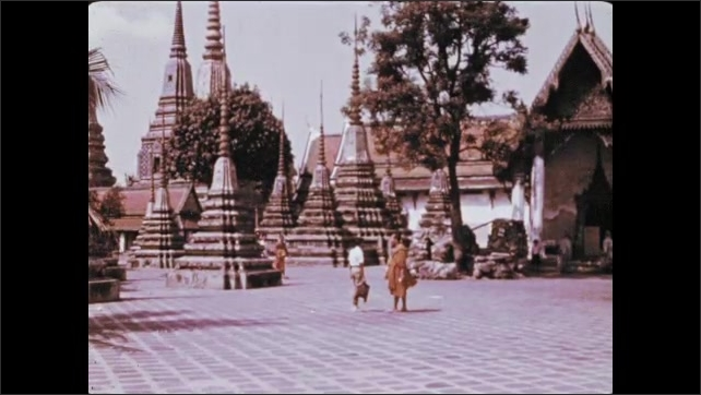 1970s: Man stares. Buddhist monk sits and meditates. People walk around Buddhist temple compound. Large ornamental, decorative, Asian style buildings.