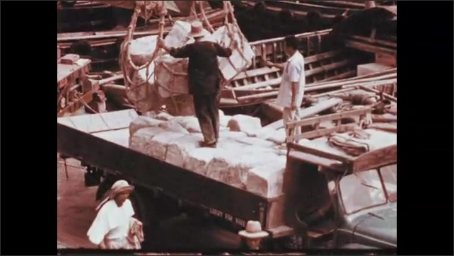 1970s: People work in fields, load cargo on docks, travel through city, canoe down river.