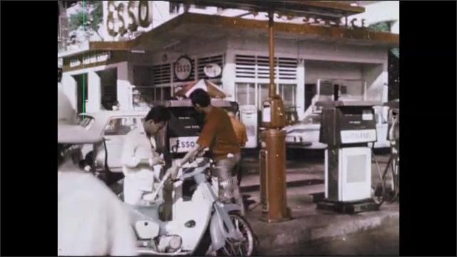 1970s: Farmers walk in circle with oxen. Men fill scooter with petrol at gas station. Man paints small statue near miniatures. Man works on papers at office desk. Men work on aircraft engine.