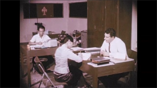 1970s: People walk on sidewalk near busy city street. Man sits at office desk and talks to woman. Women writes on paper as man speaks at office desk.