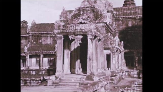 1970s: Statues of men flank canal. Stone-lined road leads to ornate city. Angkor Wat temple and city stands in jungle. Monks walk near ornate temple.