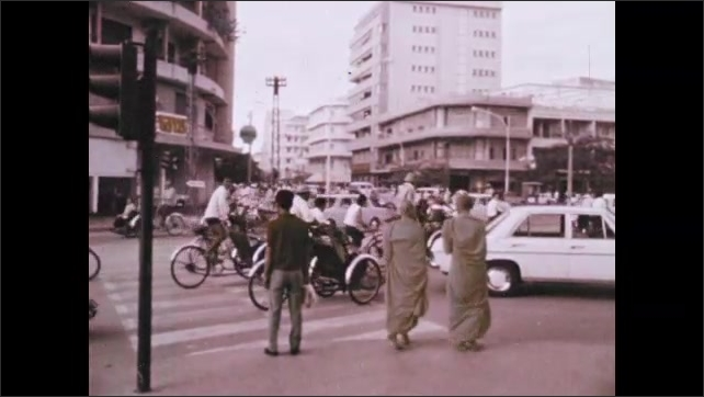 1970s: Cars and pedestrians navigate the city streets of Phnom Penh. Workers operate machines and box up product in small factory.