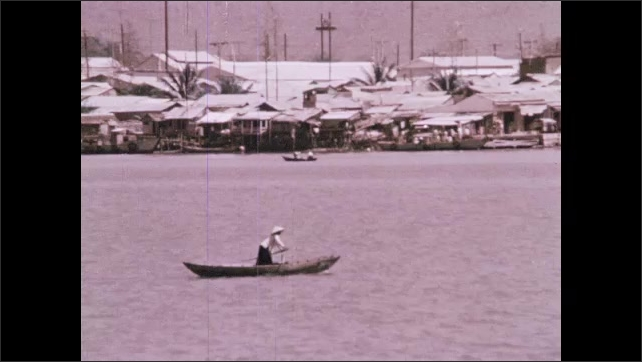 1970s: People buy and sell vegetables in street market. Man rows boat down Red River. Men ride motorboat past cruise and cargo ships at mouth of Red River.