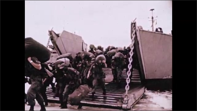 1970s: Soldier speaks to troops near large chalkboard. American soldiers disembark boat onto shores of Vietnam. Soldiers carry sacks and weapons across beach.