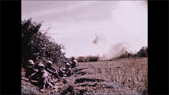 1970s: Soldiers run through tall grass toward hills. Planes bomb hills. Soldiers sit near sandbags. Helicopter flies over Mekong River. Jungle camp burns in forest.