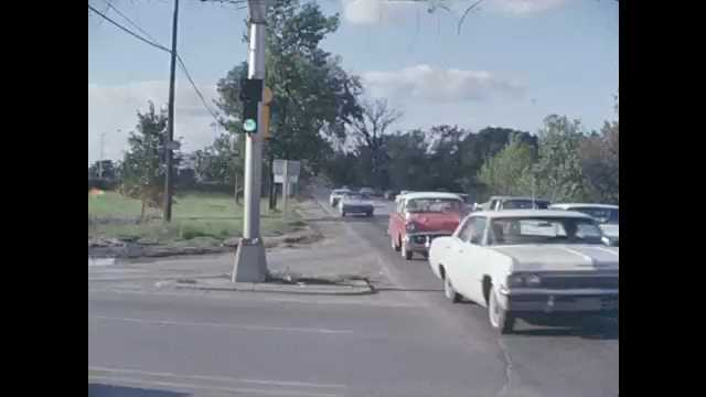 1960s: Traffic traveling through busy intersection. Zoom in on traffic light turning red.