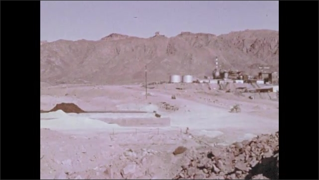 1970s: Baren, rocky landscape. Jeep drives by. Factory, refinery. Shore of body of water.