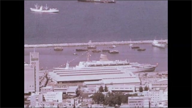 1970s: Cargo is unloaded by crane from boat at dock. Cruise ship and commercial ships at docks in port.