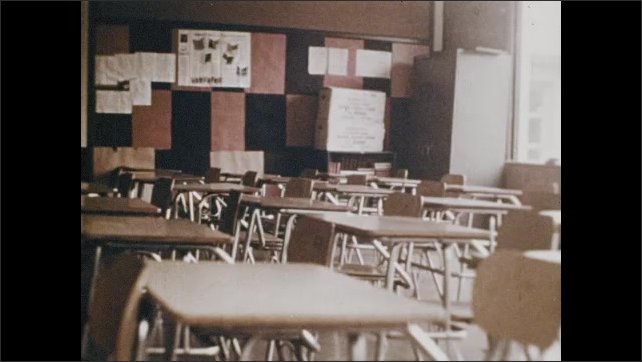 1970s: Fast motion, tracking shot into school building. Shots of classroom. Fire alarm. Gym, Trophies. Sign above door. Classroom. Sink. Sign above door. Classroom. Views of doors. Sign.