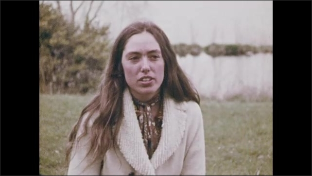 1970s: Close up, goose eating from hand. Woman sitting on ground, talking. Tracking shot, woman walking toward building.