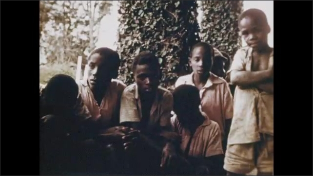 1970s: Still images, view of hill through window. Villagers by building. Children posing. Group of boys. Exterior of bulding. Man at desk. Man with woman and kids at desk. Woman with kids.