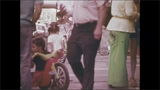 1970s: Woman talking, pan to man sitting on stoop. People on sidewalk. Woman talking on sidewalk.