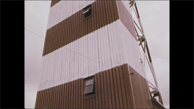 1970s: Still images, men in flight control tower. Man with backpack. Control tower. Man by river. Man talking into radio. View of man. Runway. Tilt up control tower. Man in tower. Plane landing.