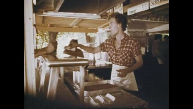 1970s: View of fast food restaurant. Hand cooking hot dogs, tilt up to man. Man working in restaurant. Rear view, man talking through window in restaurant. Zoom in on man. Close up of man.