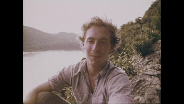 1970s: Man talking next to river. High angle view of reservoir, tracking shot to man writing.