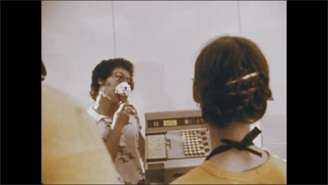 1970s: Close up of woman talking. Tracking shot of people by counter. Woman talking. Man lifts crate of milk.