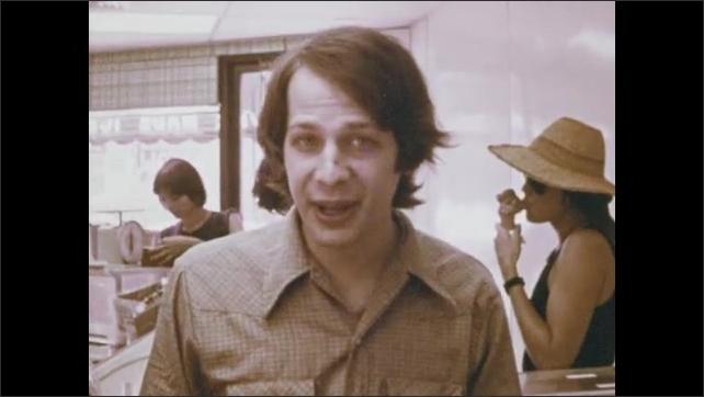 1970s: Man talking in ice cream shop.